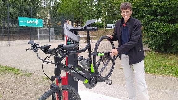 Ein Mann steht neben der Fahrradreparaturstation.