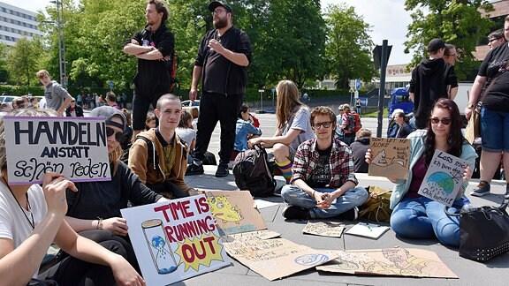 Schüler mit gebastelten und bemalten Pappschildern auf der Fridays for Future Demo in Chemnitz.