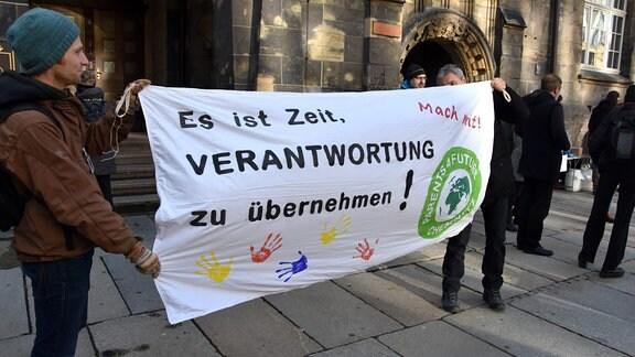 Zwei Personen halten ein Banner mit der Aufschrift - ''Es ist Zeit Verantwortung zu übernehmen''.