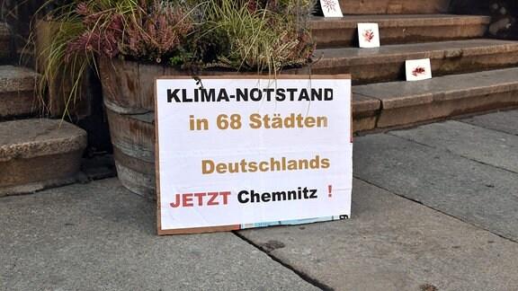 Plakat Klimanotstand lehnt an einem Pflanzenkübel.