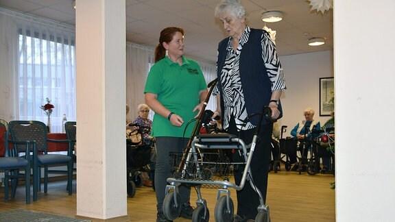 EIne ältere Frau mit Rollator steht vor einem Hinderniss. Eine Frau in grünem Oberteil und der Aufschrift ''Verkehrswacht'' spricht mit ihr.