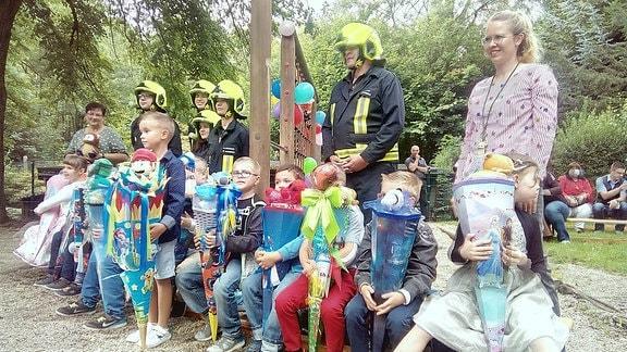 Kinder auf einer Bank und dahinter Feuerwehrleute lachen für ein Gruppenfoto.