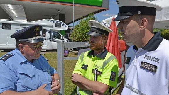 Ein deutscher Polizist unterhält sich mit zwei Kollegen aus Tschechien.