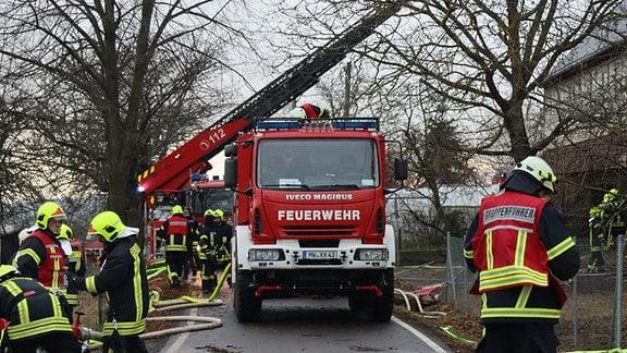 Feuerwehrlleute richten sich am Einsatzort ein. Eine Drehleiter wird positioniert und Löschschläuche verlegt.