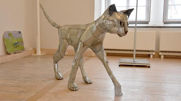 Eine aus Blechen zusammengenietete Katze steht in einem Ausstellungsraum.