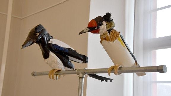 Zwei Vögel aus gesammelten Abfällen sitzen auf einer Stange in einem Ausstellungsraum.