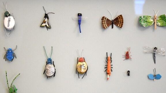 Insekten aus Kronkorken und Bonbonpapier werden in einem Glaskasten präsentiert.