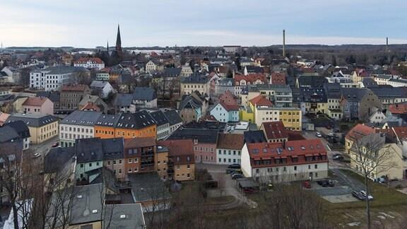 Blick von einer Anhöhe auf eine Kleinstadt. Unter anderen sind zwei Kirchtürme und drei Fabrikschlote zu sehen.
