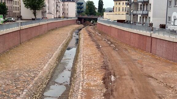 Blick in einen breiten gemauerten Graben, in dessen Mitte ein kleiner Bach fließt
