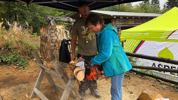 Frau schneidet mit einer Kettensäge eine Baumstamm