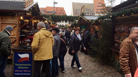 Menschen inmitten geschmückter Weihnachts-Verkaufsstände.