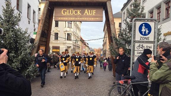 Eine Parade unter einem Tor mit der Beschriftung Glück auf.