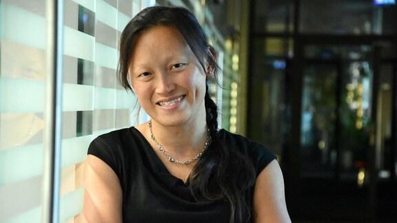 Die Forscherin Roh Pin Lee, TU Freiberg, lehnt an einem Fenster und schaut lächelnd in die Kamera.