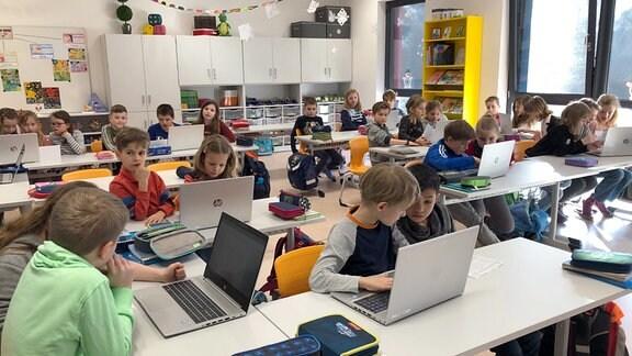 Kinder vor Laptops an der Schulbank sitzend.