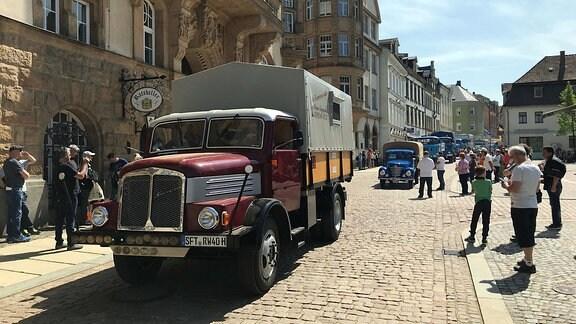 Ein historischer Lkw vom Typ S 4000-1 rollt durch eine von Zuschauern gesäumte Straße