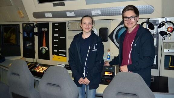 Ein Mädchen und ein Junge stehen vor einer Schalttafel,die das Cockpit eines Raumschiffes simuliert