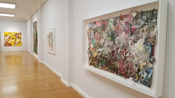 Ausstellungsraum mit großen, farbigen Bildern und Collagen