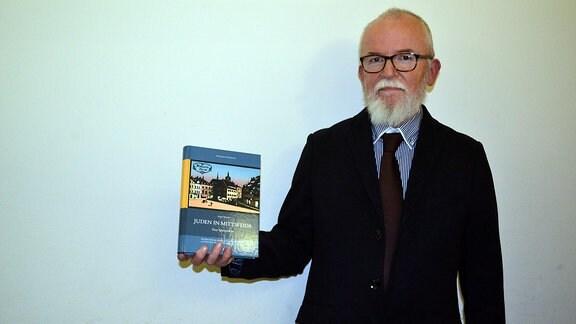 Ein Mann mit Bart und Brille hält ein Buch in der Hand, mit dem Titel Juden in Mittweida