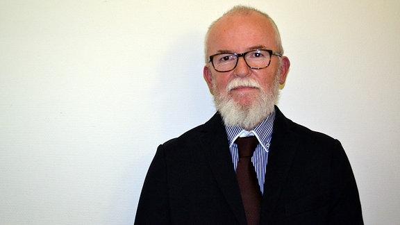 Portraitfoto eines Mannes mit Bart und Brille