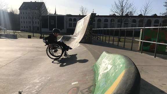 Ein Junge mit Helm sitzt im Rollstuhl und rollt eine Skaterrampe hoch.