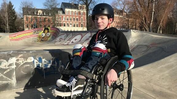 Ein Junge mit schwarzem Schutzhelm sitzt im Rollstuhl und lächelt in die Kamera. Die zu klein wirkenden Beine sind am Rollstuhl festgeschnallt.