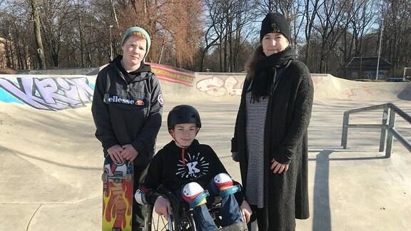 In einem Skaterpark sitzt ein Junge im Rollstuhl, rechts und links neben ihm stehen sein jüngerer Bruder und seine Mutter.