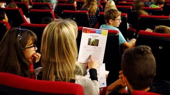 Kinder sitzen in einem Kinosaal auf roten Kinosesseln.