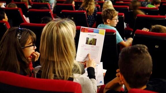 Kinder sitzen in einem Kinosaal auf roten Kinosesseln