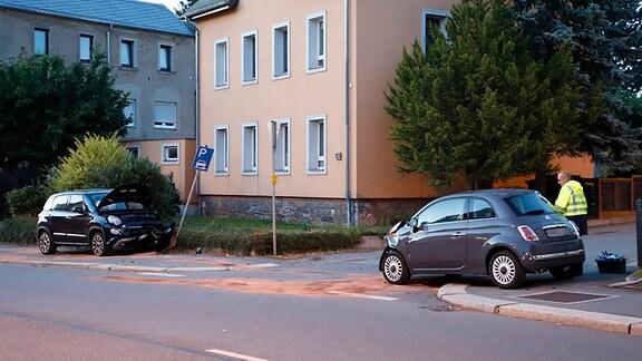 Zwei Kleinwagen sind zusammengestoßen und stehen etwas entfernt voneinander auf einer Straße