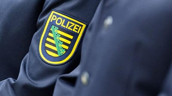 Wappen der sächsischen Polizei ist an einem Uniform angebracht, aufgenommen bei der feierlichen Vereidigung in der Sachsen-Arena den Eid ab.