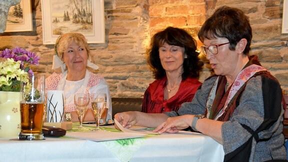 Drei Frauen, eine davon in Tracht, sitzen an einem Tischvor einer Natursteinwand. Eine von ihnen liest einene Text vor