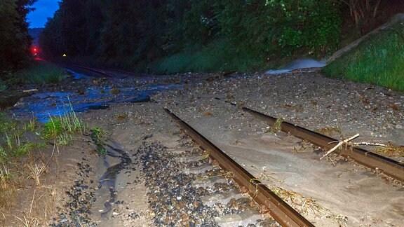 Von Schlamm und Geröll überschwemmte Zuggleise
