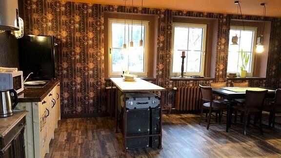 Eine Küchenzeile, Tische und Stühle stehen in Einem Raum mit drei Fenstern.