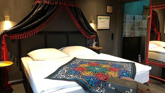 Ein weißes Doppelbett steht in einem Raum mit dunklen Wänden.