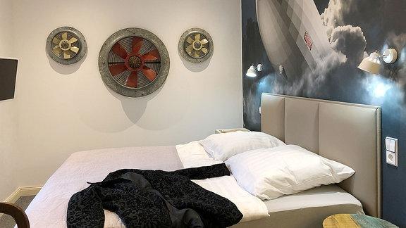 Hinter einem Doppelbett hängt ein Bild von einem Zeppelin.