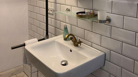 Ein Spiegel, gebaut aus einem Dachfenster, hängt über einem Waschbecken.