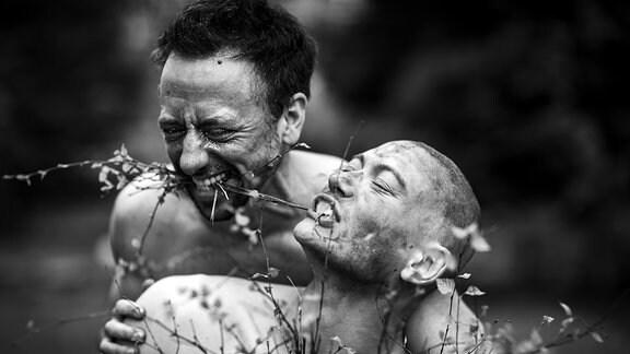 Zwei Personen mit nackten Oberkörpern, einer mit Zweigen im Mund, freuen sich entspannt in der Natur