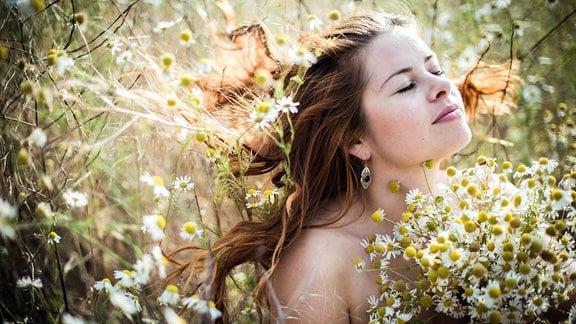 Eine Frau mit langen Haaren und nackten Schultern hält einen Blumenstrauß auf einer Wiese