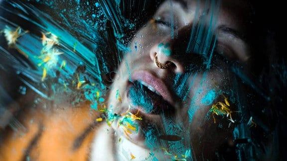 Hintere einer Glasscheibe mit farbigen Streifen: ein Gesicht, geöffnete Lippen, ein Nasenpiercing
