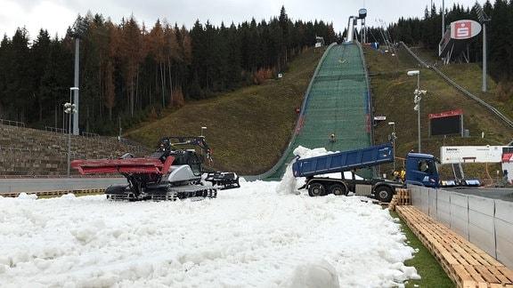 Im Auslauf der Vogtlandschanze Klingenthal wird mit einem Lkw und einer Raupe Kunstschnee ausgebreitet.