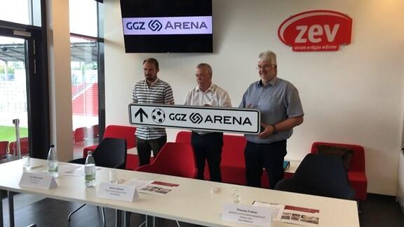 """Toni Wachsmuth (Sportdirektor FSV Zwickau), Rainer Kallweit (Geschäftsführer der Stadion Zwickau Betriebsgesellschaft) und Thomas Frohne (Geschäftsführer der Gebäude- und Grundstücksgesellschaft Zwickau) halten ein Hinweisschild mit dem Namen """"GGZ-Arena"""" in den Händen"""