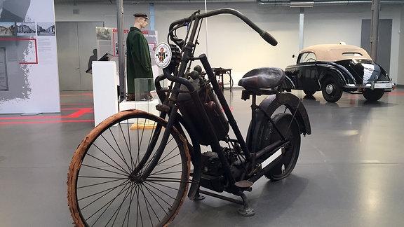 Ein Motorrad der Firma Hildebrandt und Wolfmüller von 1895 steht in einer Ausstellung