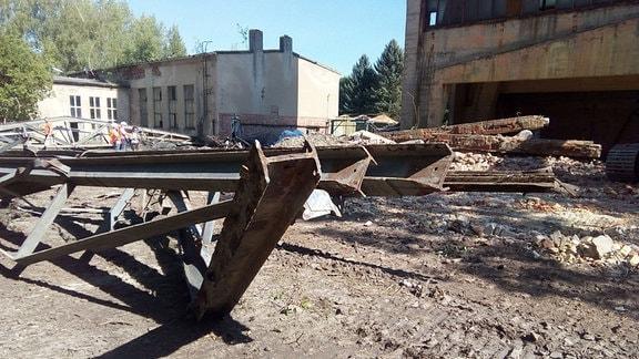 Auf einer Schuttfläche vor Ruinen lagern verbogene Stahlträger.