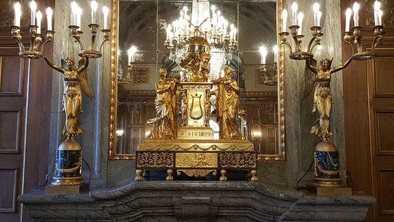 Auf einem Kaminsims in einem Schloss stehen eine große goldene Uhr und zwei Engel.