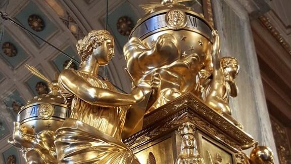 Auf einem Kaminsims in einem Schloss stehen eine große goldene Uhr, davor eine große goldene Figur.