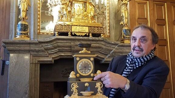 Ein Mann sitzt vor einem Kamin in einem Schloss und zeigt zwei große Standuhren.