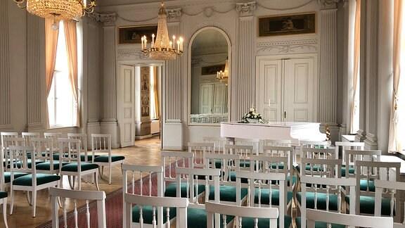 Im Stil des Klassizismus weiß getäfelter und reichlich verzierter Festsaal. Blick von hinten auf eine Theaterbestuhlung von weißen Stühlen mit grünen Samtbezogenen Sitzpolstern. Vorn ist ein großer Wandspiegel, zwei Türen sowie ein weißer Flügel zu sehen.