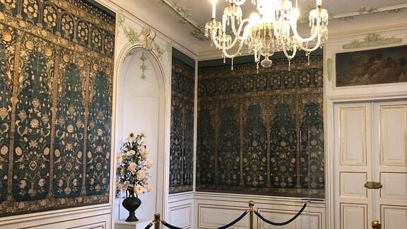 Zu sehen sind zwie Wände eines abgedunkelten Salons des Schlosses. Die Wände sind mit seidig glänzender dunkelblauer Tapete bespannt, die reichlich und kleinteilig mit Blumen-, Vögel und Vasenmotiven verziert ist. Die filigranen Stuckverzierungen sind in dunkel-türkiser Farbe angemalt. Von der Decke hängt in der Mitte des Raumes ein großer Deckenkronleuchter herunter.