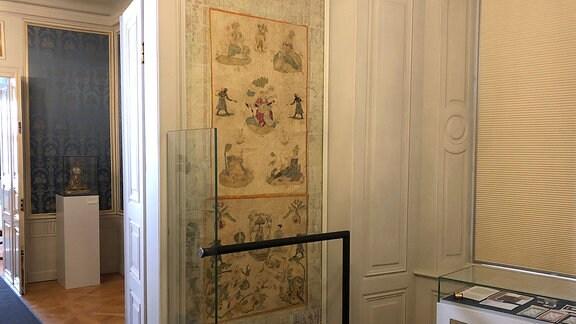 In einem kleinen Raum mit abgedunkeltem Fenster ist an einer Wand neben der Tür eine alte Seidentapete mit chinesischen Motiven zu sehen.