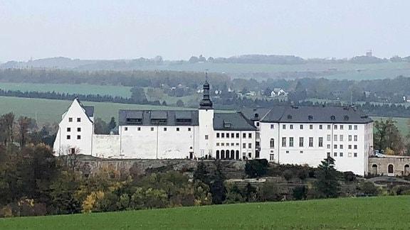 Blick auf ein langgezogenes weißes Schloss inmitten einer hügeligen Herbstlandschaft.